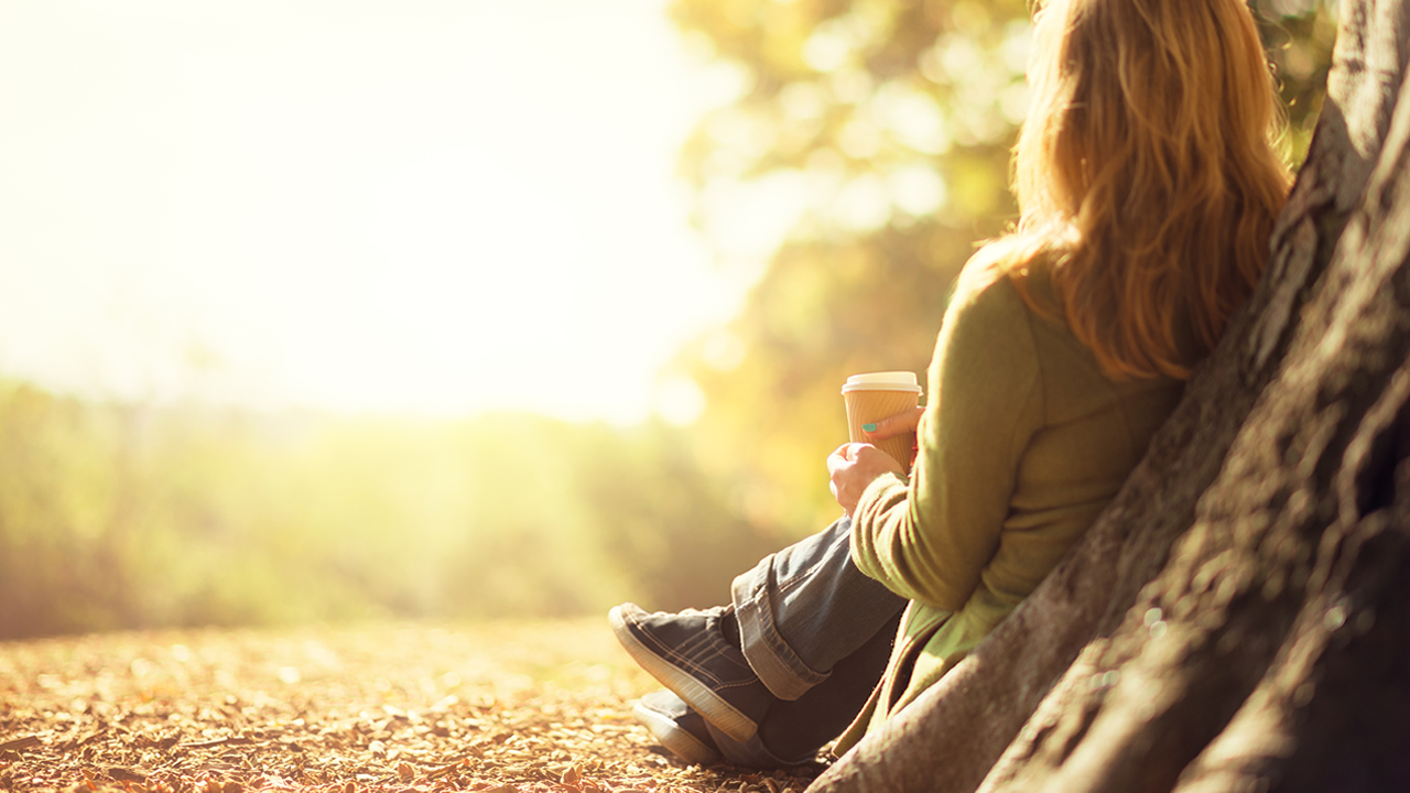 woman sitting by tree drinking coffee