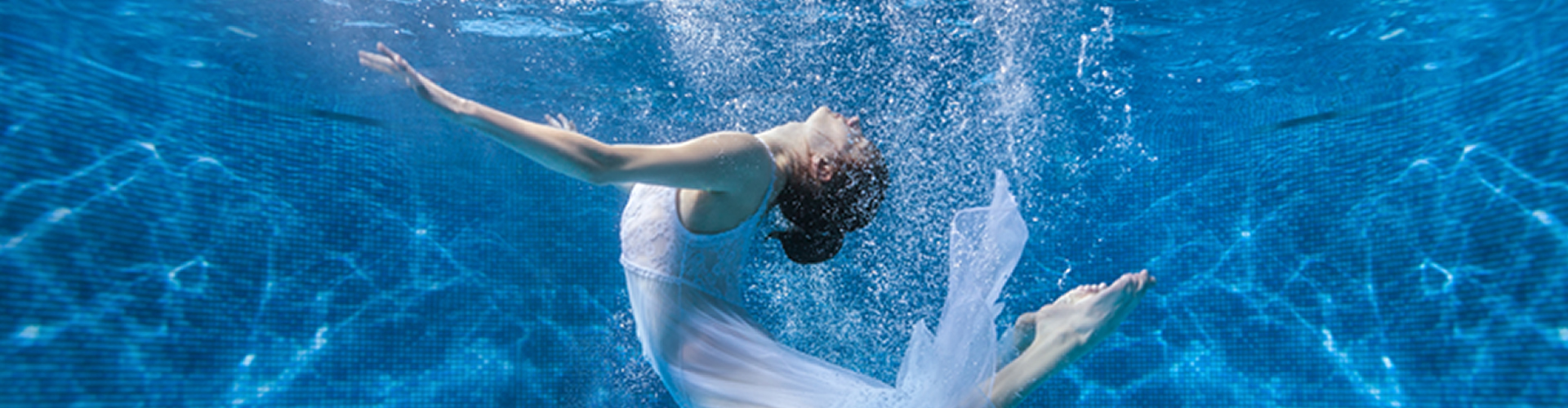 Woman floating in pool arched back